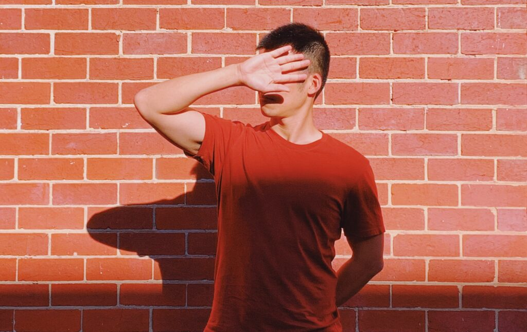 Helping Your Clients Reclaim Their Voice. Image shows person standing in front of brick wall, head turned away, hand up blocking their face.