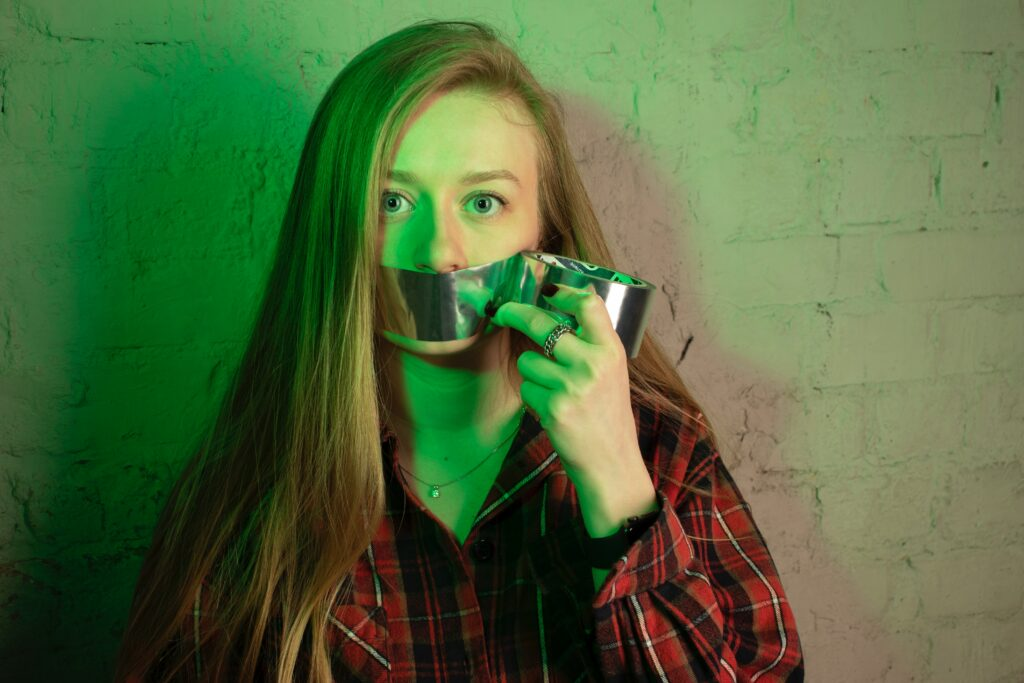 Helping Clients Reclaim Their Voice. Image shows person putting duct tape on their own mouth.