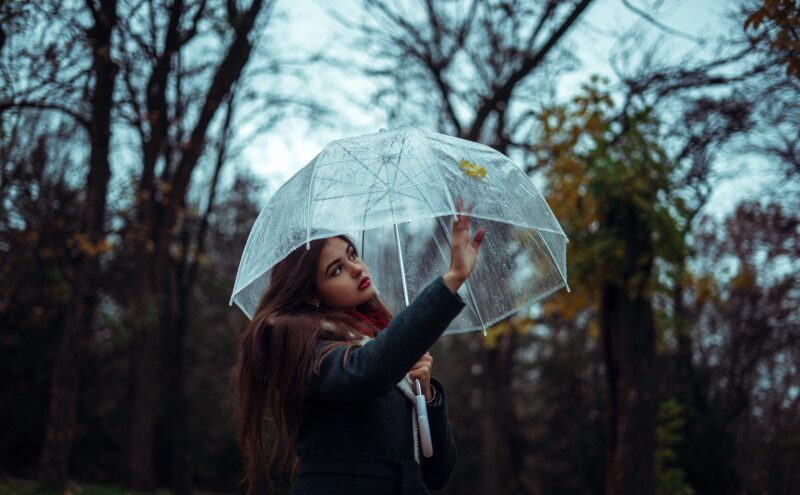 A woman shows resilience in the rain by using an umbrella.
