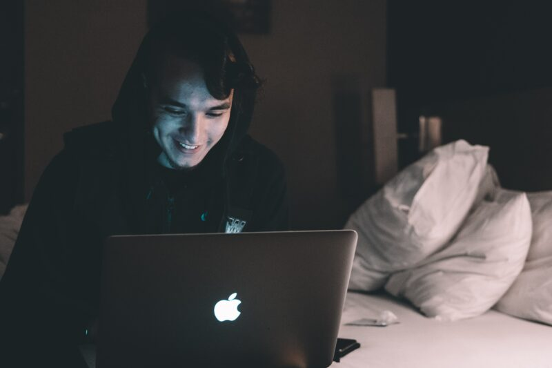A man in a long-distance relationship chats with his partner on a laptop.