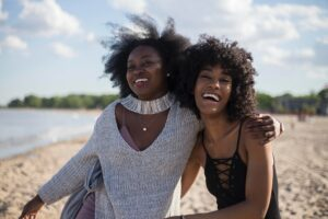 Two friends smile and revel in the power of peer support.