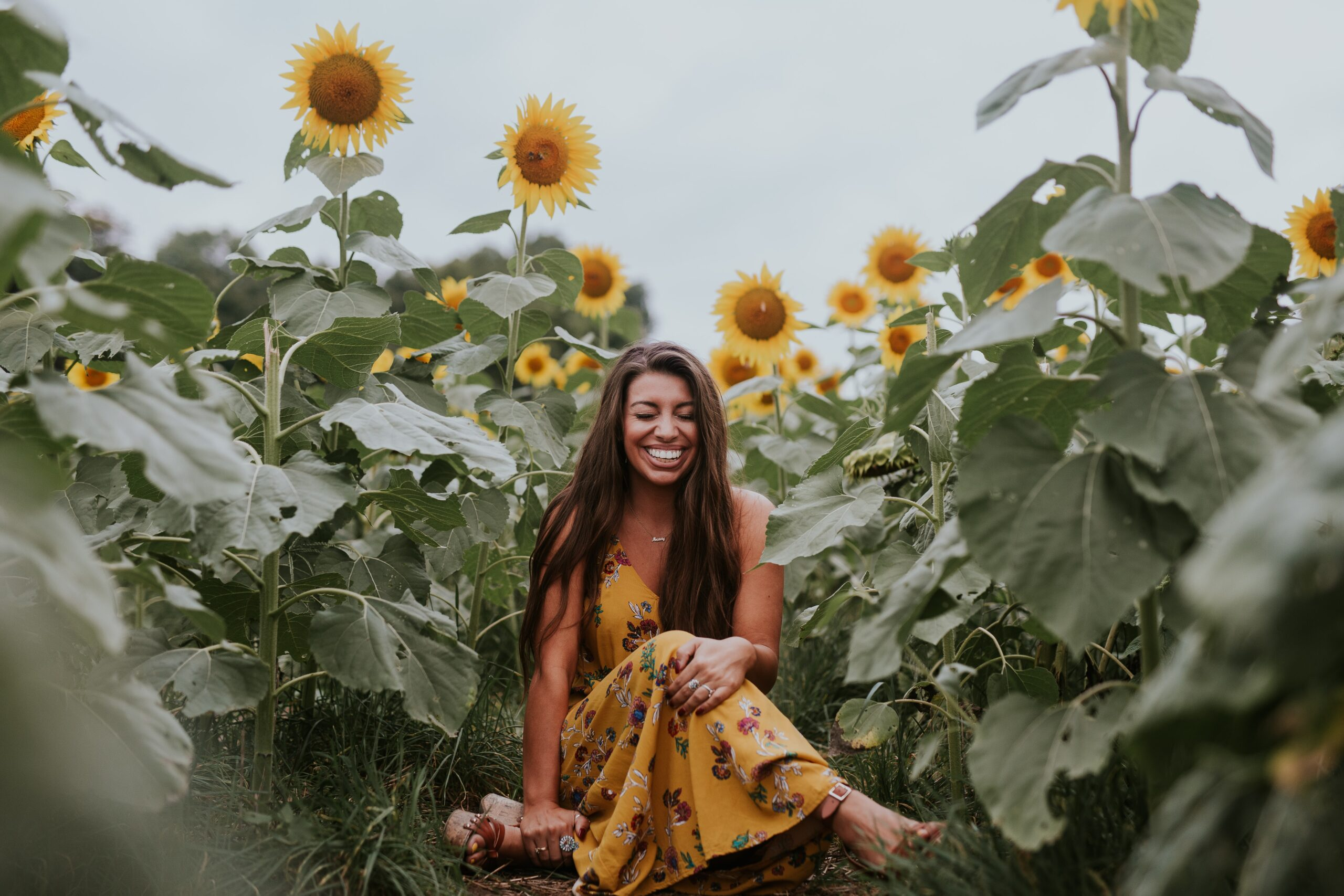 A woman sits in a field of flowers as a form of self-care.