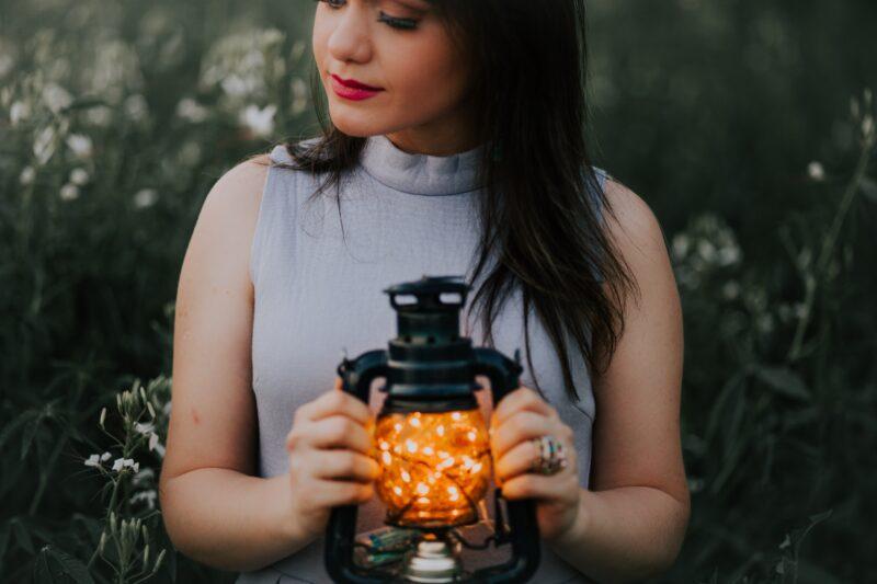 A woman holding a lantern exudes calm energy.