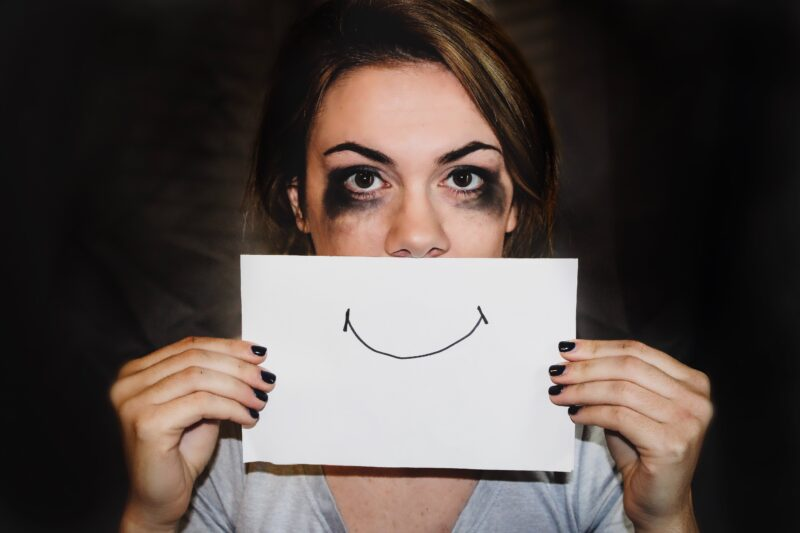 A woman wears a drawn smile to hide sadness about IPV