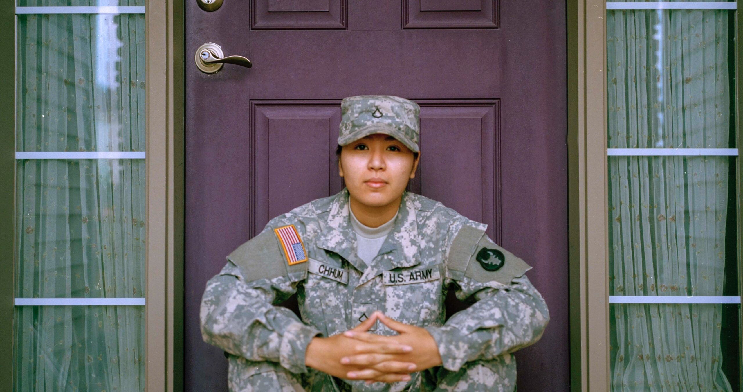 A woman who is part of a military couple sits in front of a door.