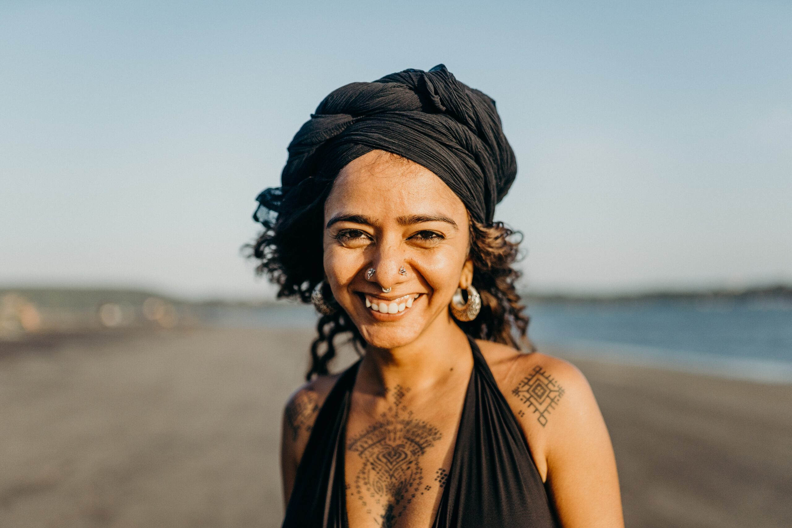 Image shows smiling woman on the beach