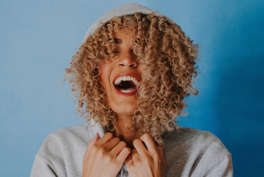 Clearing Your Container: Image shows woman with curly hair laughing