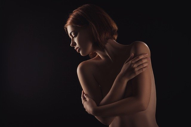 Skin Hunger: Image shows nude person hugging self while looking to side