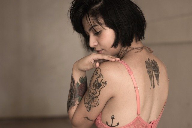 Skin Hunger: Image shows tattooed woman looking back over shoulder