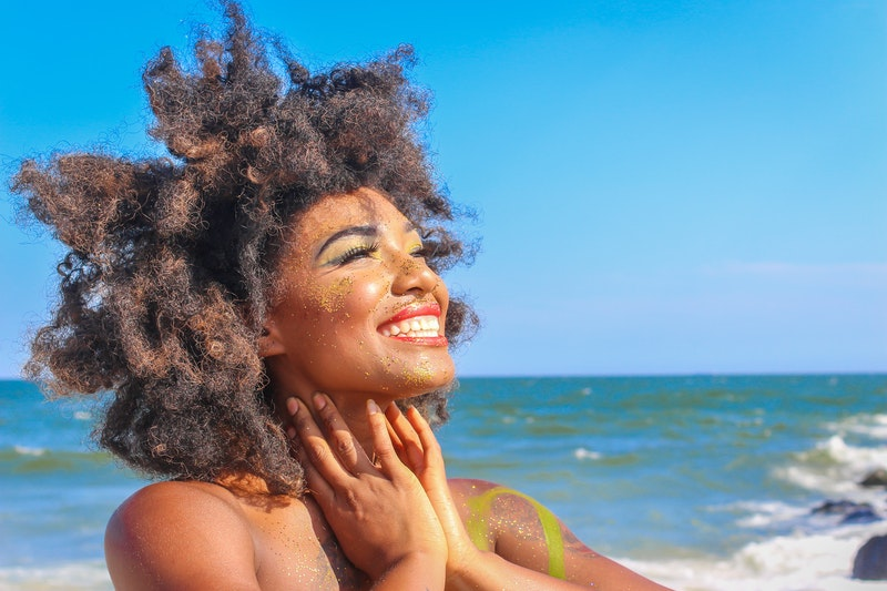 A woman smiles about the soothing benefits of self pleasure