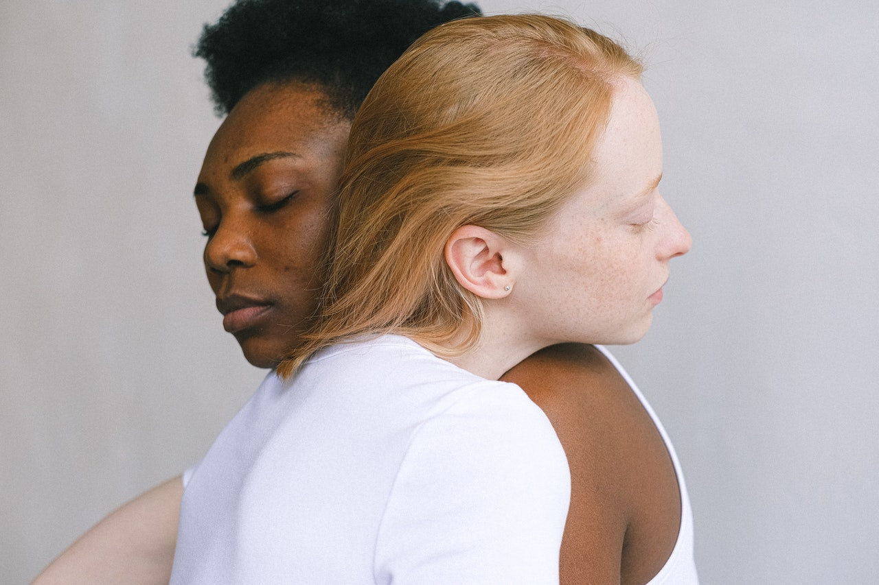 two people resting their heads on each other's shoulders