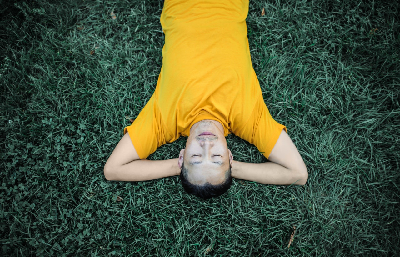 man lying in the grass upside down