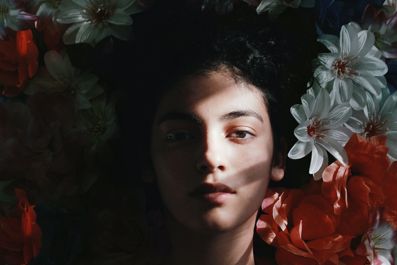 woman with a shaded face laying in flowers