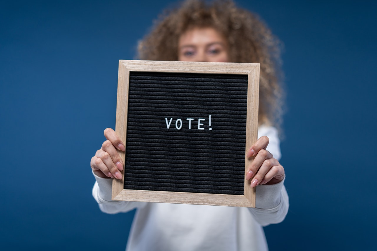 woman holds a sign that says vote