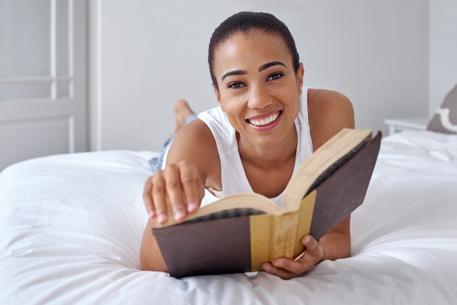 woman lays in bed and smiles while reading a sex book