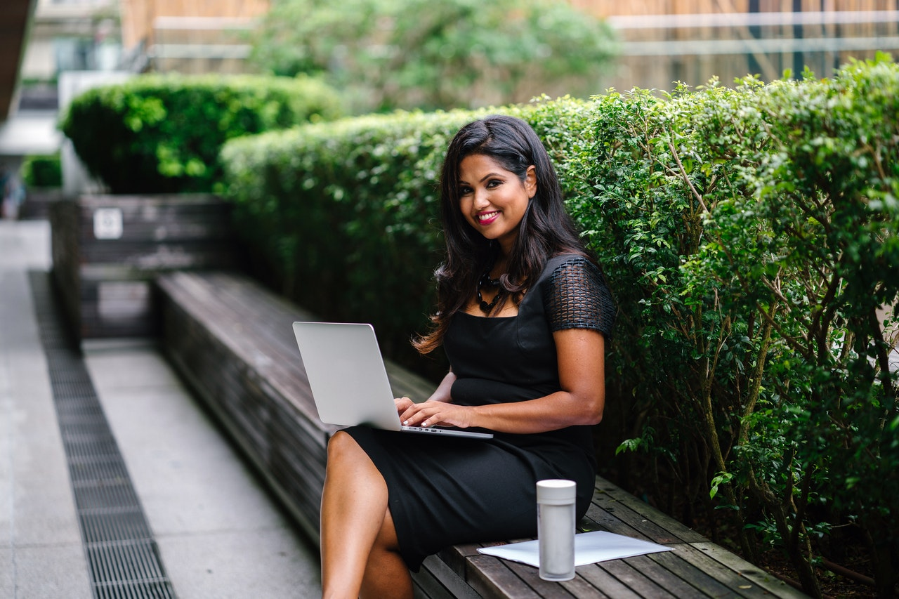 woman sitting on a bench with a laptop working with sexual shame in women