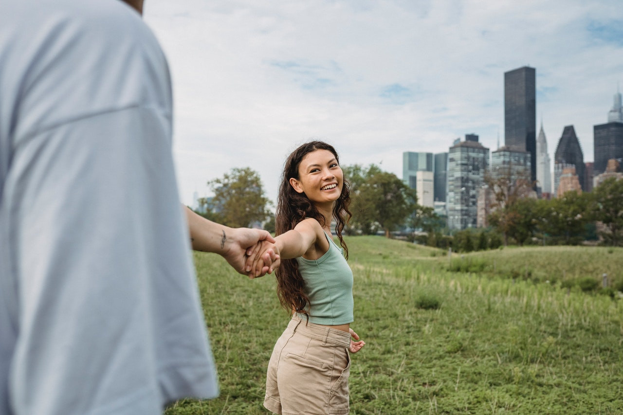 a happy couple holding hands in a field practicing gratitude for better sex