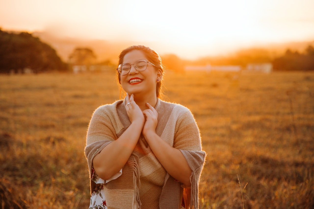 woman smiling in a field practicing gratitude for better sex