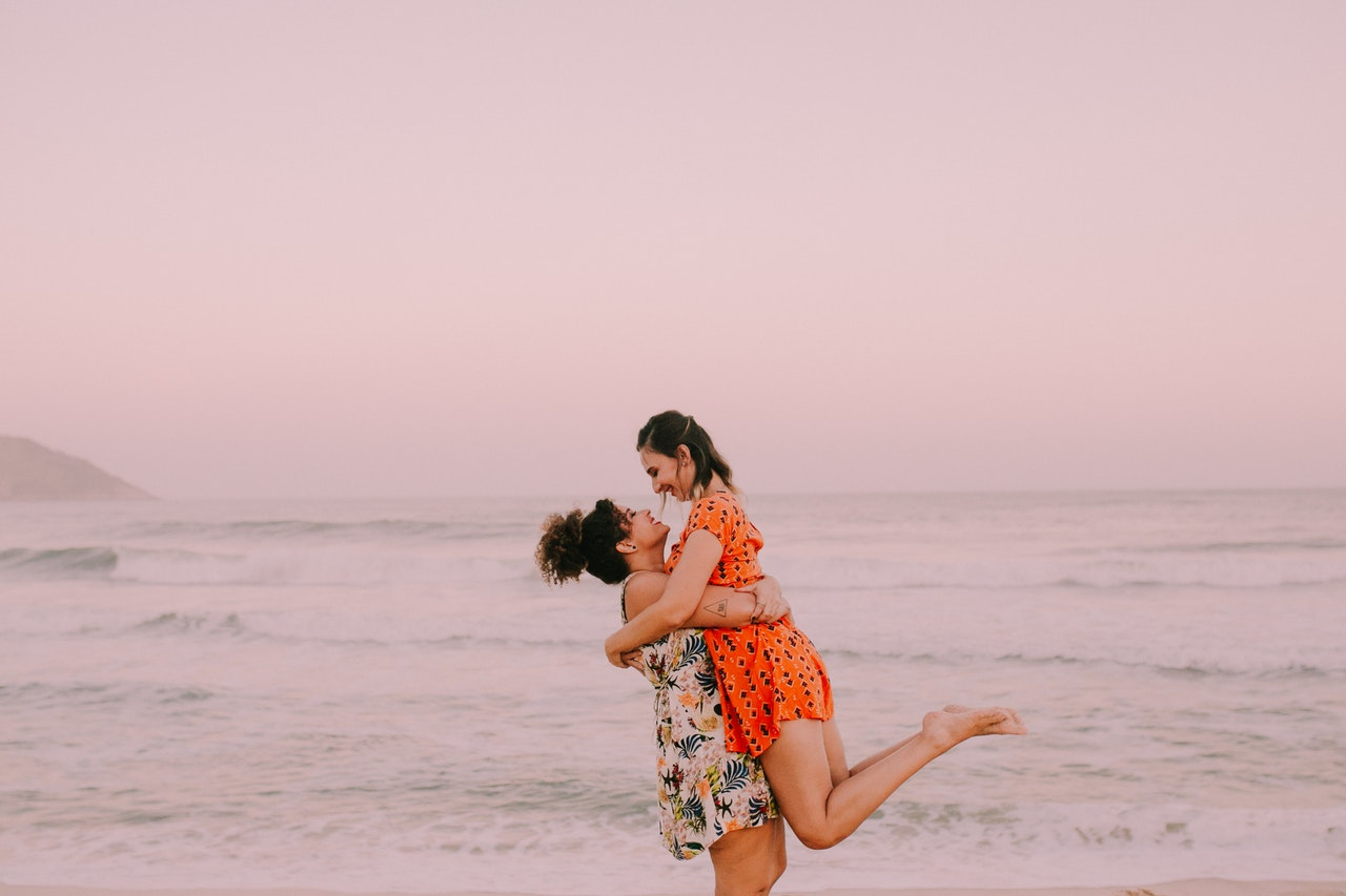 a couple holds each other on the beach in happiness because they have utilized the five love languages