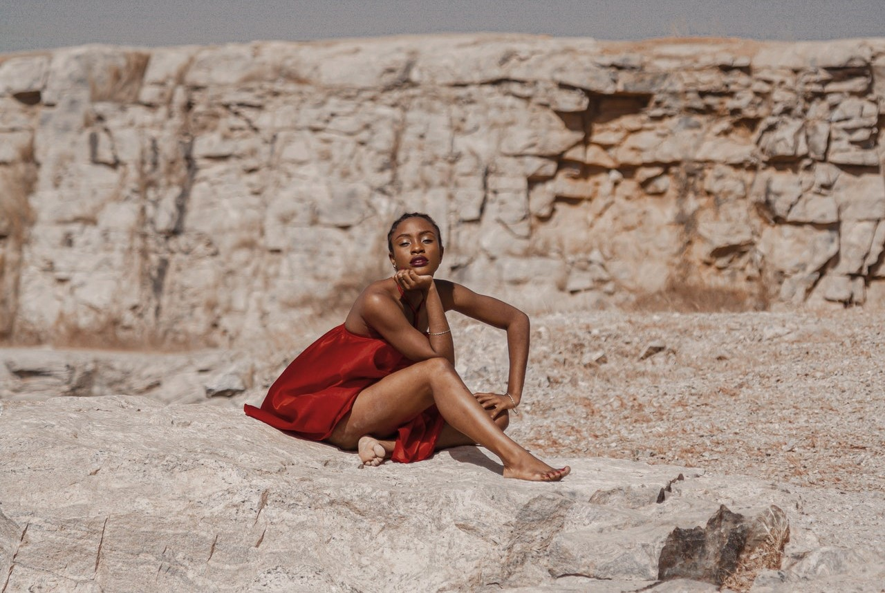 an aries woman in a red dress sits in a power pose on rocks