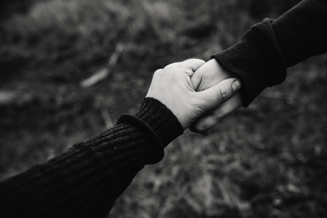 black and white photo of hand holding representing compassion in sex positive puberty