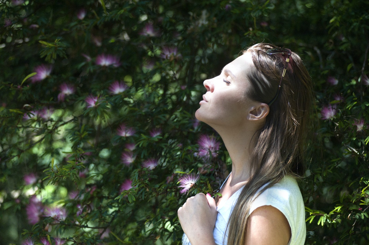a woman in a meadow meditating and using mindfulness to beat performance anxiety