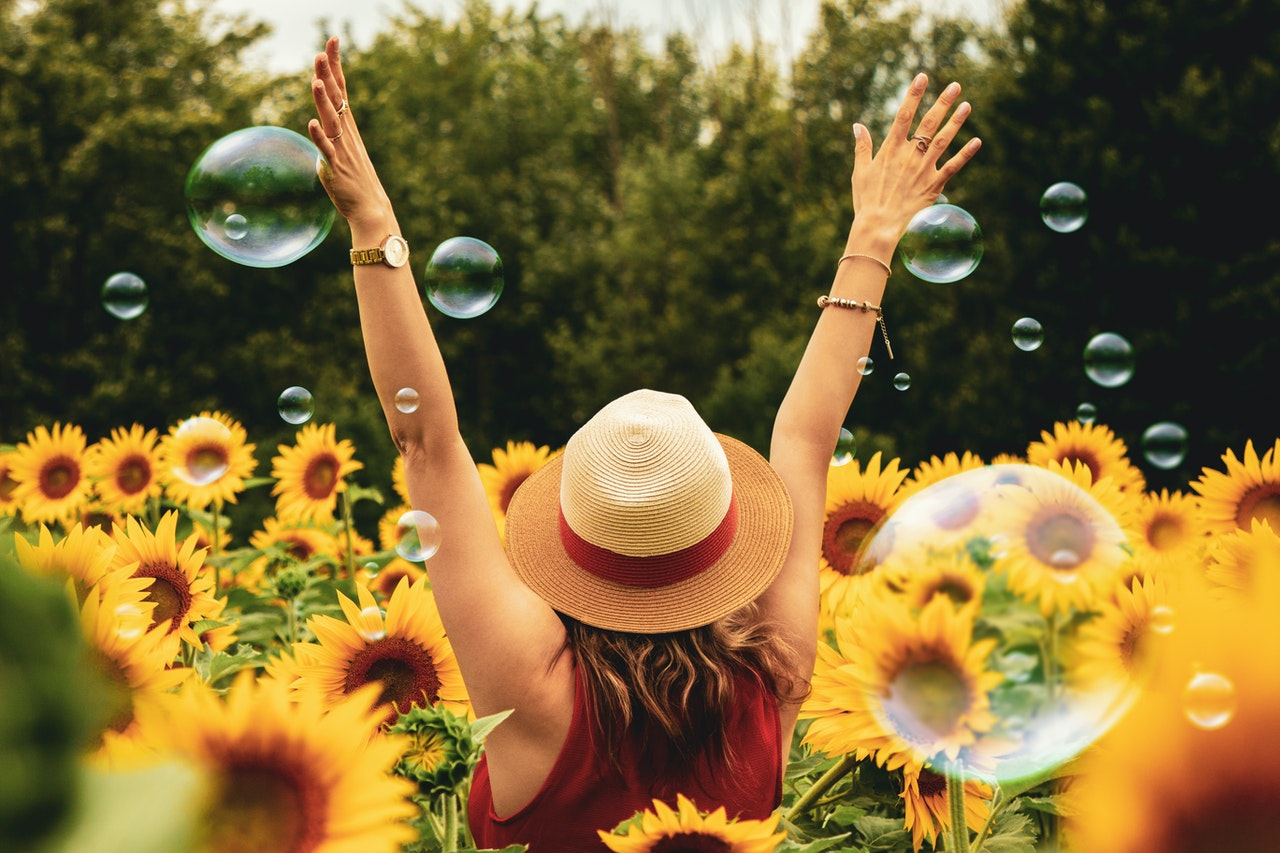 a woman with her arms up in a sunflower field with bubbles feeling joyful in fitness and sex coaching