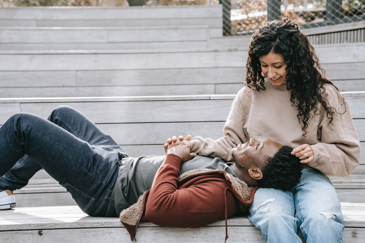 a man lays on a woman's lap representing Cancer relationship energy