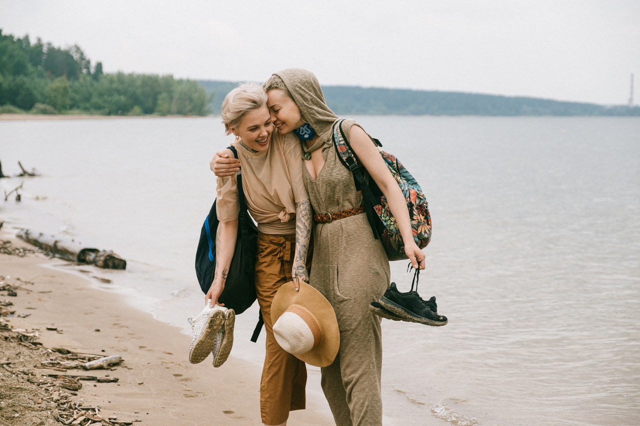 A happy Leo woman at the beach with her girlfriend
