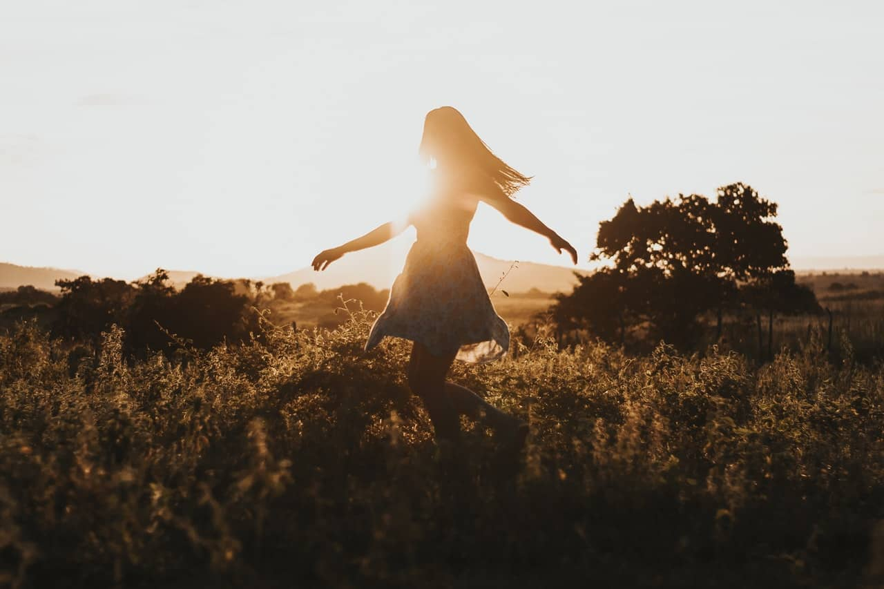 woman dances in field because she has found sustainable sex toys